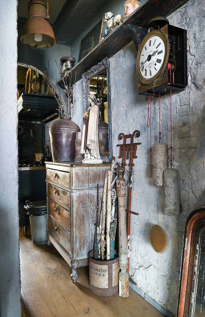 Alte Pendeluhr, Kommode und Trödel im Flur mit abgenutzter Wand
