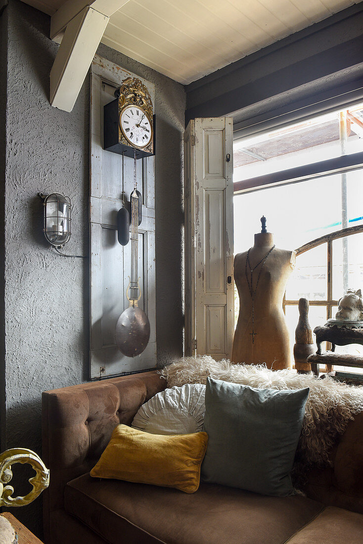 Tailors' dummy, old pendant clock and brown sofa next to window