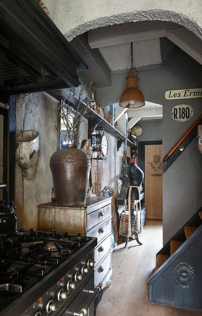 Blick von der Küche mit Gasherd in den Flur mit Trödel und Vintage-Deko