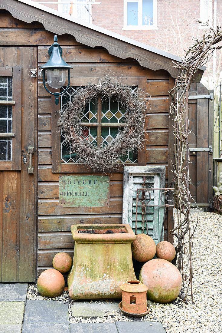 Kranz, Blumenkübel und Terracottakugeln am Gartenhaus