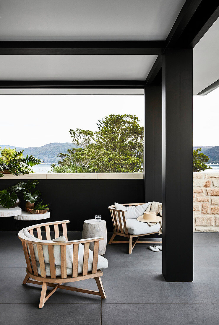 Lounge furniture on roofed terrace with panoramic view