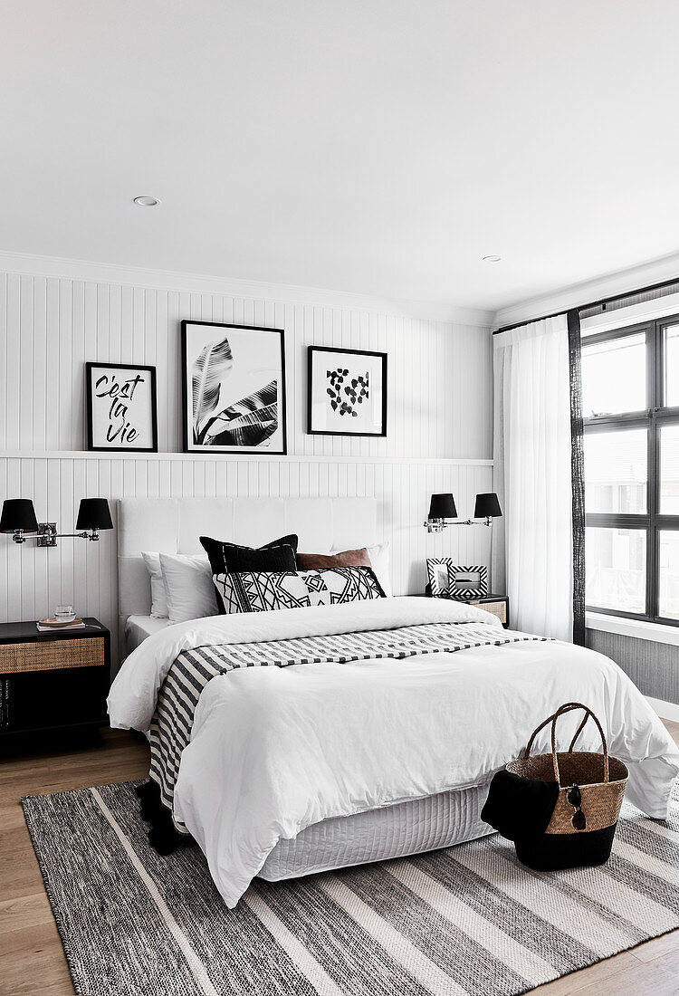 Artworks on picture ledge in monochrome bedroom