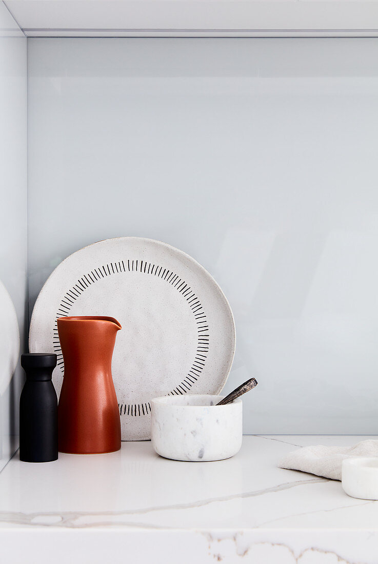 Carafe, mortar and pestle, and plate on marble worksurface