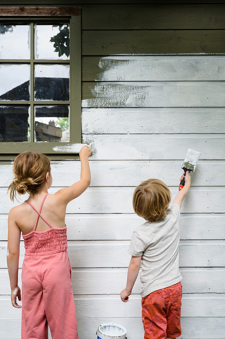 Girl (6-7) and boy (4-5) painting cottage wall