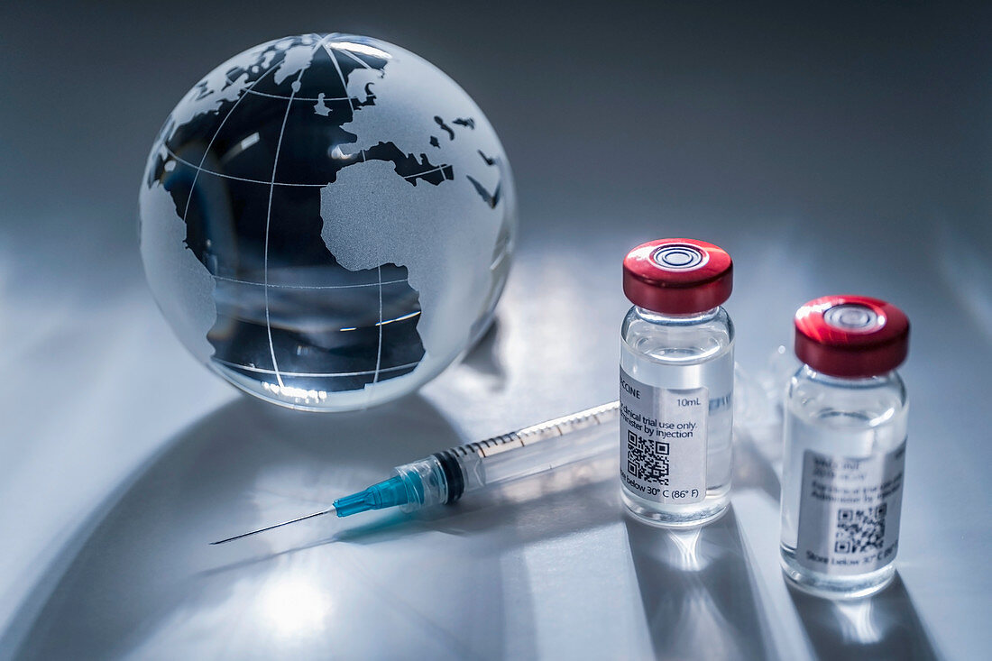 Glass globe and syringe with vaccine on gray background