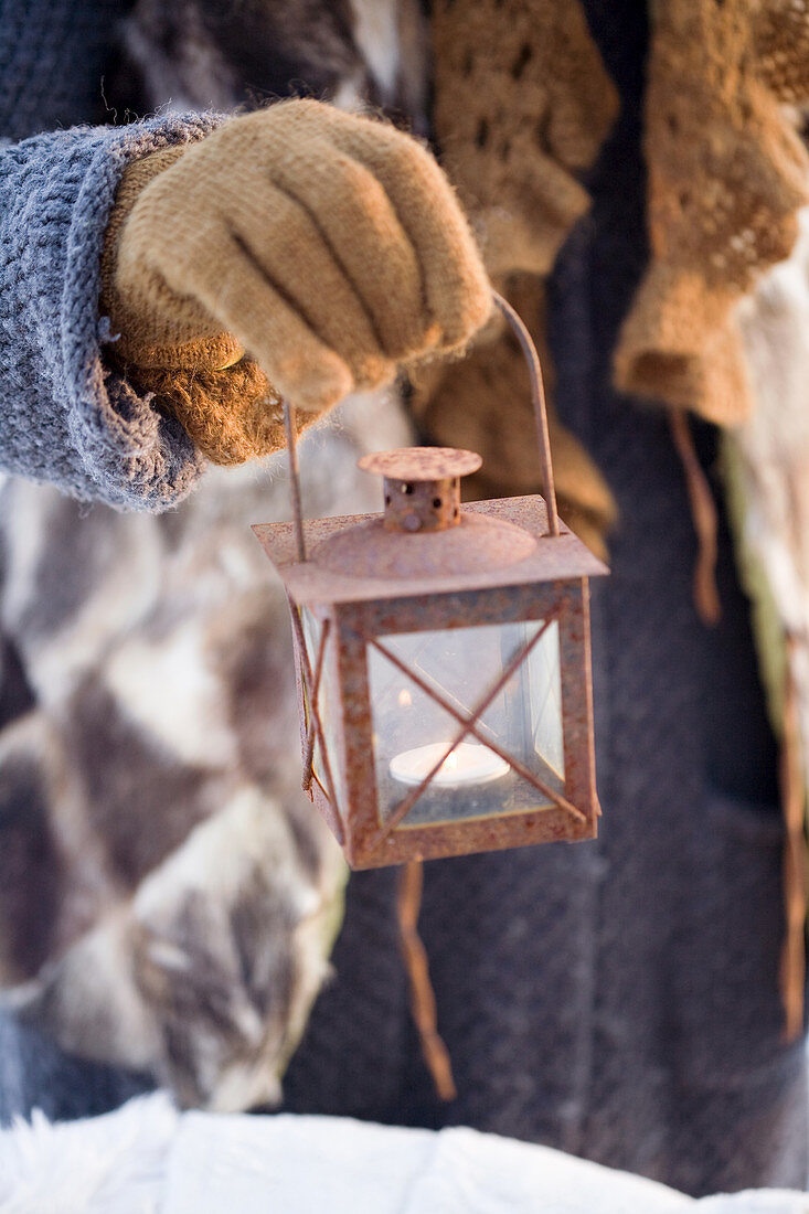 Hand with glove holding a vintage lantern
