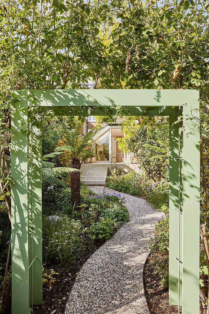 View of gravel garden path see through green-painted pergola