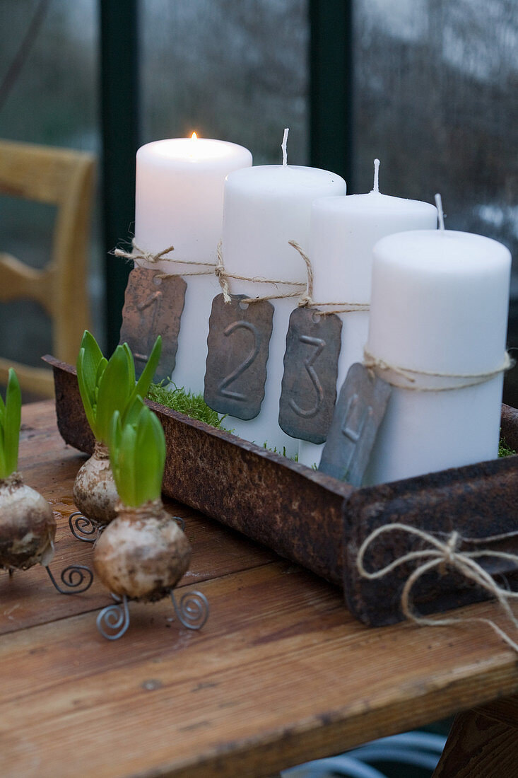 Four, white numbered pillar candles in rusty dish