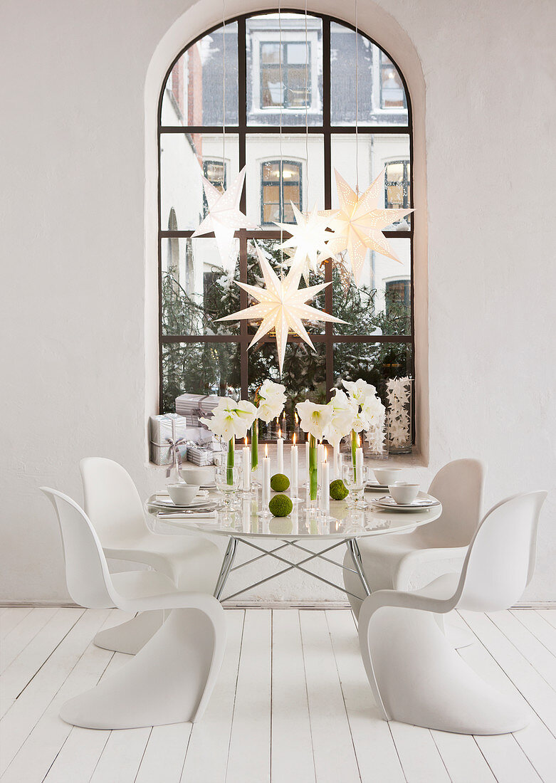 Table decorated for Christmas with amaryllis and white classic chairs