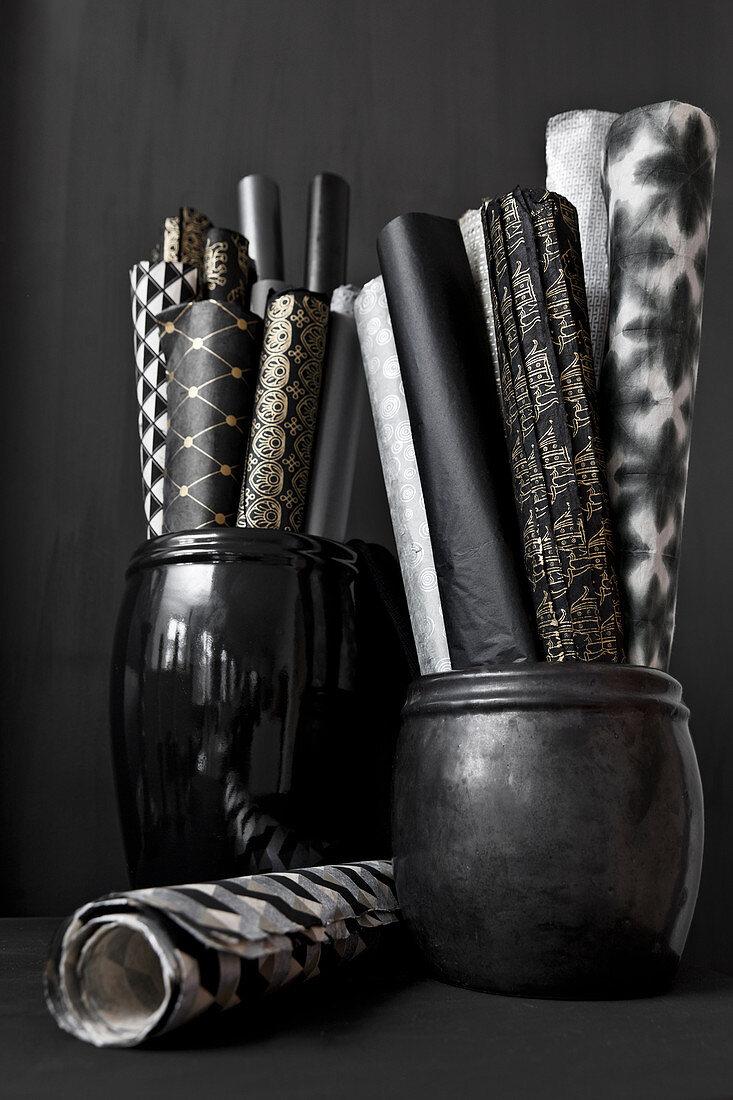 Rolls of paper in black pots