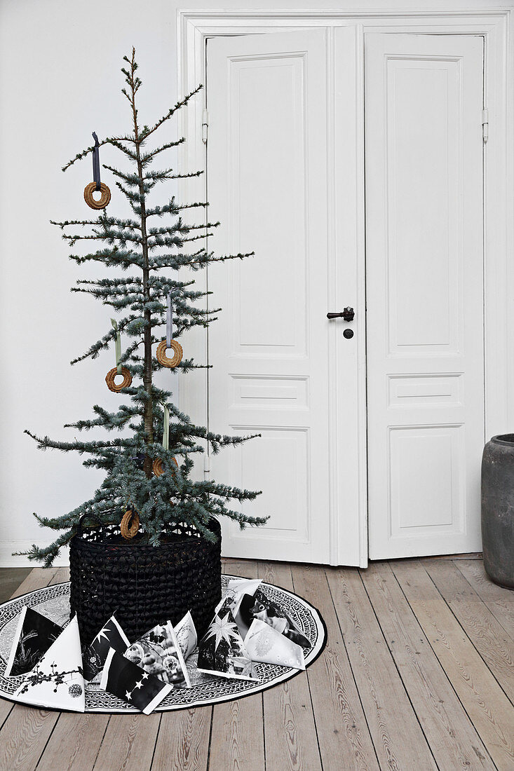 Decorated tree in basket and gift bags in front of interior doors