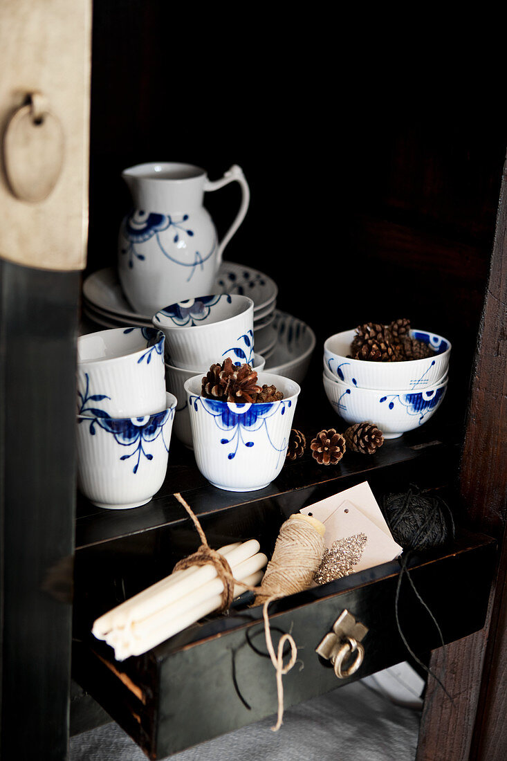 Arrangement of blue-and-white crockery and conifer cones