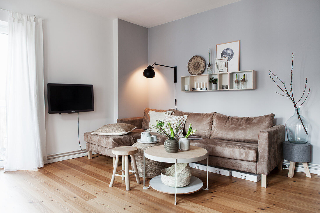 Sand-coloured sofa, wall-mounted lamp and coffee table with vases of white flowers