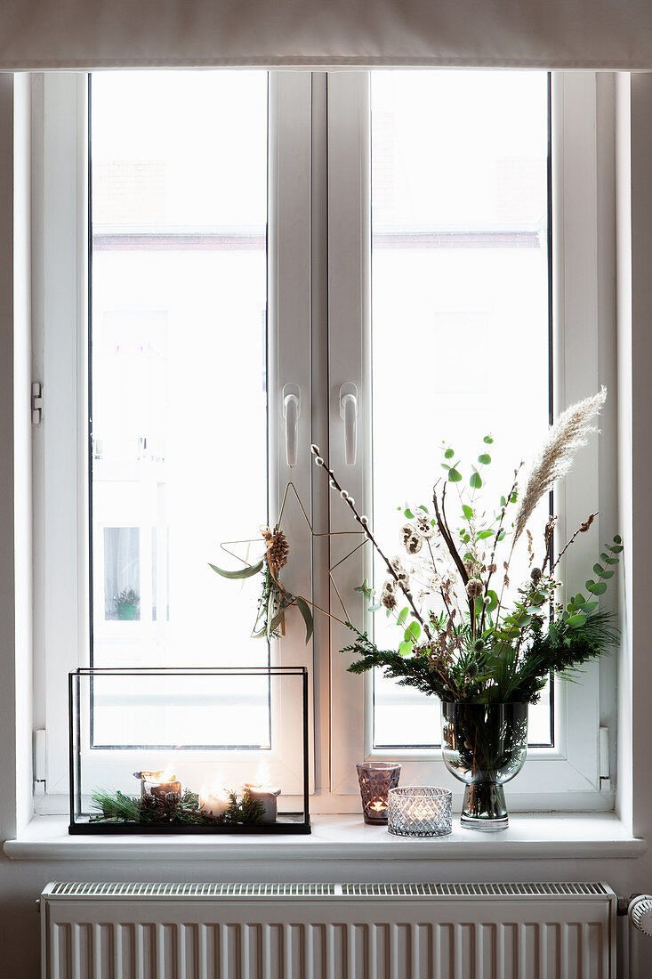 Bouquet and candle lanterns on windowsill