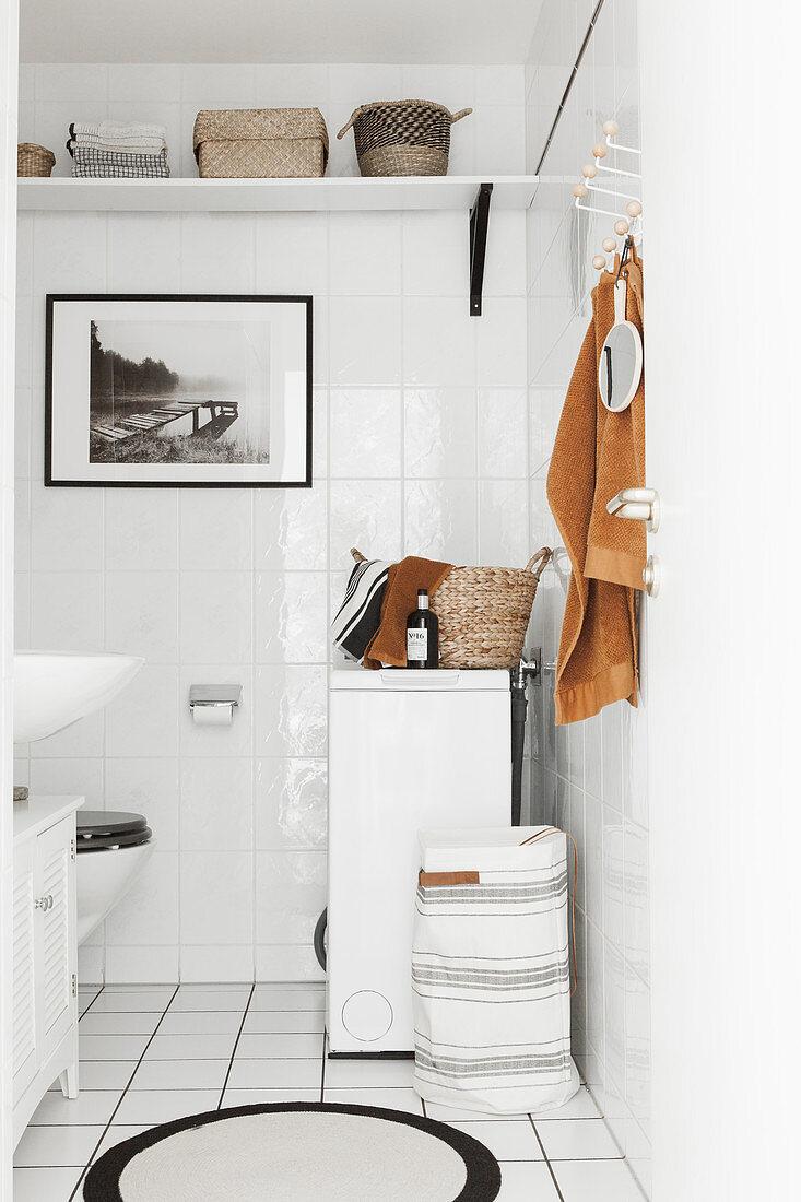 Washing machine in white-tiled bathroom