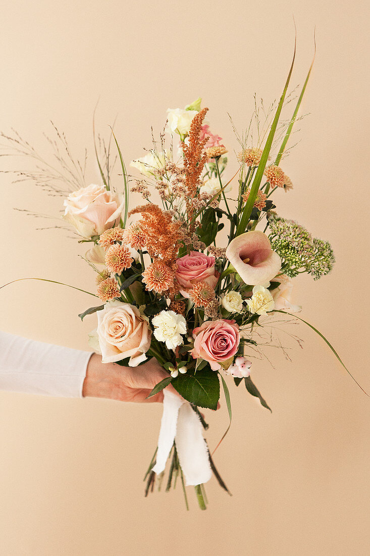 Hand holds bouquet with roses, calla lillies, chrysanthemums, carnations, amaranth, stonecrop, sea lavender and grass