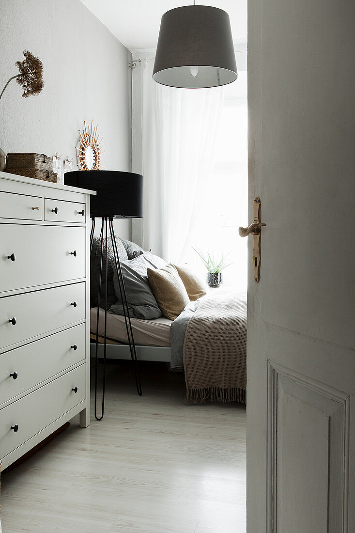 View past chest of drawers to bed and standard lamp in bedroom