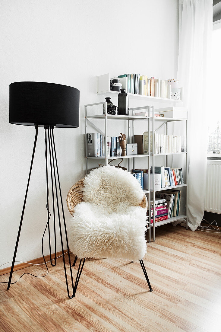 Black standard lamp and easy chair with sheepskin rug in front of shelves