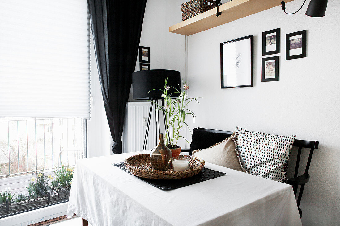 Table with white tablecloth, black bench and standard lamp in corner