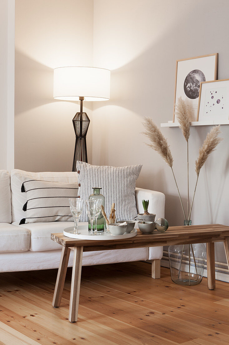 Scatter cushions on white couch, dried pampas grass in vase and snacks on coffee table