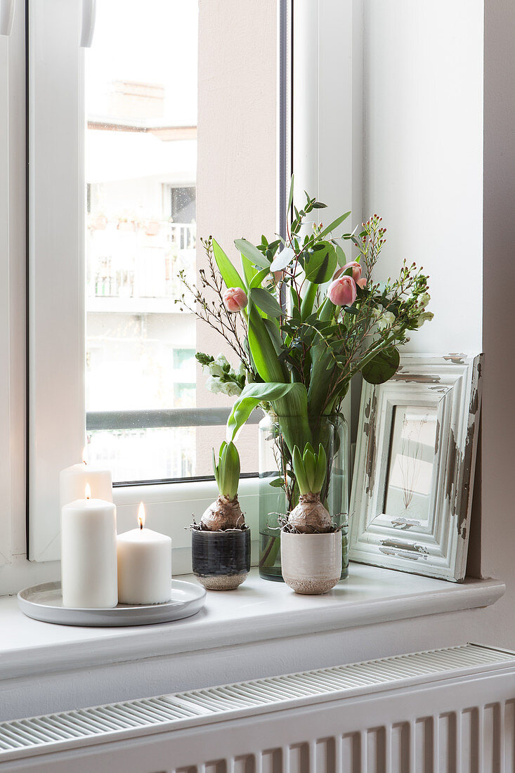 Spring bouquet of tulips and white candles on windowsill
