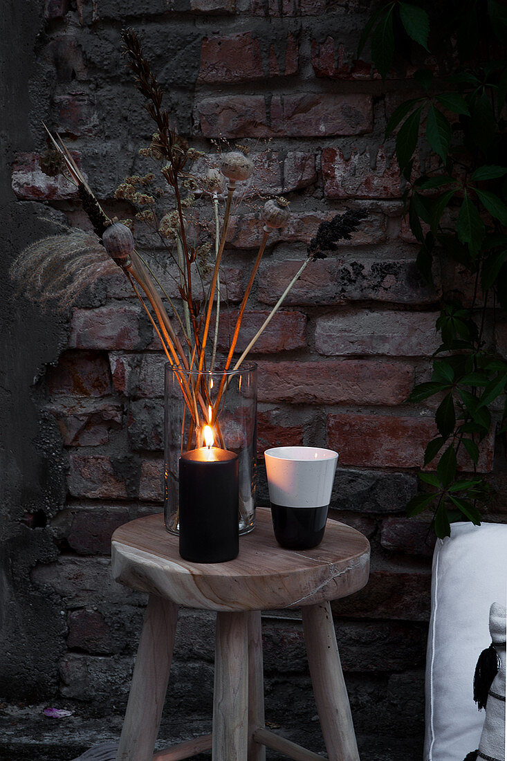Dried flowers, candles and beakers on wooden stool
