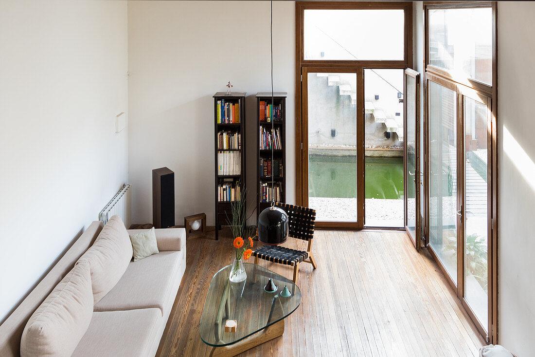 Wohnzimmer mit heller Couch, Glastisch und Bücherregal neben Terrassentür