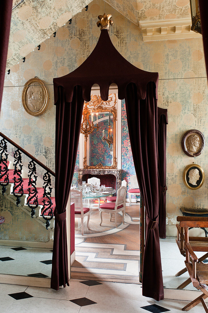 Burgundy curtains, wrought iron staircase, Roman plaster cameos and foil wallpaper in hallway