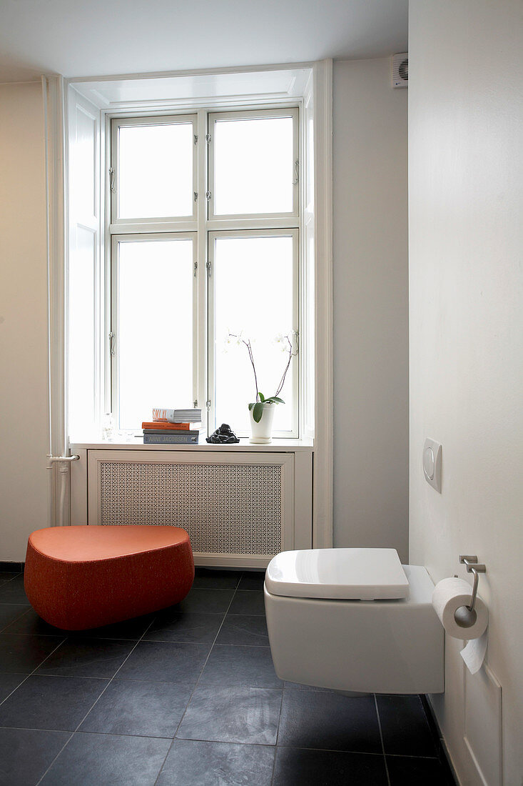 Toiled and orange stool in bathroom
