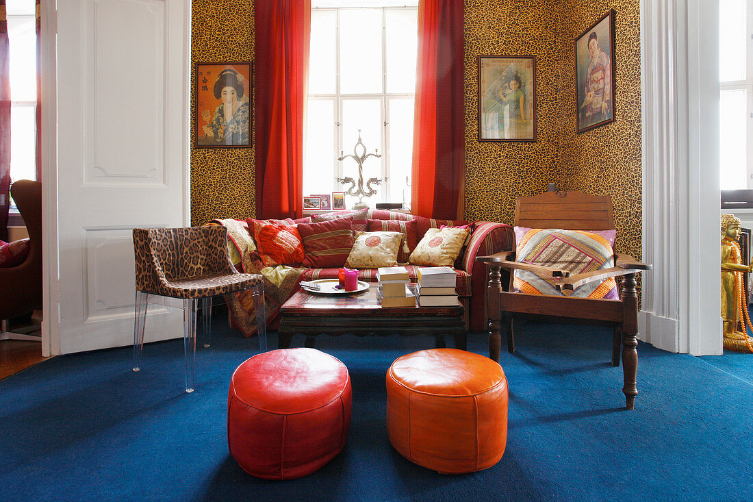 Leopard-print wallpaper, red curtains and deep blue carpet in lounge