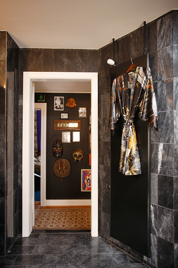 Kimono hanging on bathroom wall with dark marble tiles and view into hallway with decorated wall