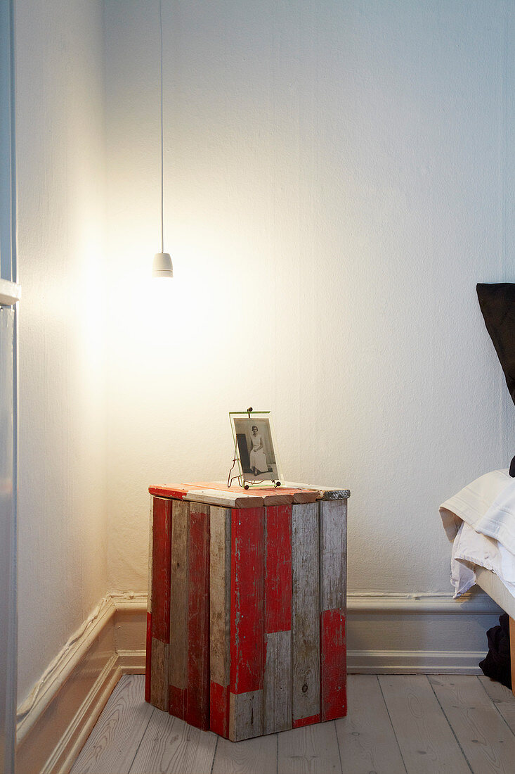 Vintage wooden crate, partially painted red, used as bedside table