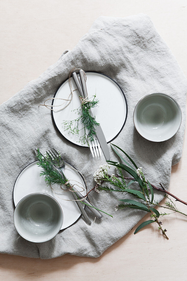Cutlery bound as posies with sprigs of leaves