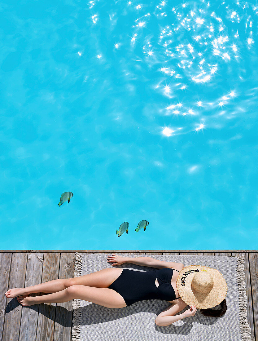 Woman wearing swimsuit lying by swimming pool with straw hat over face