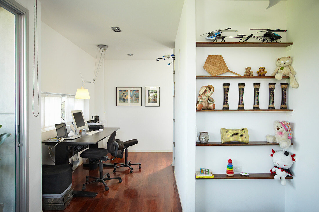 View into study with black desk; childhood mementoes on shelves in foreground