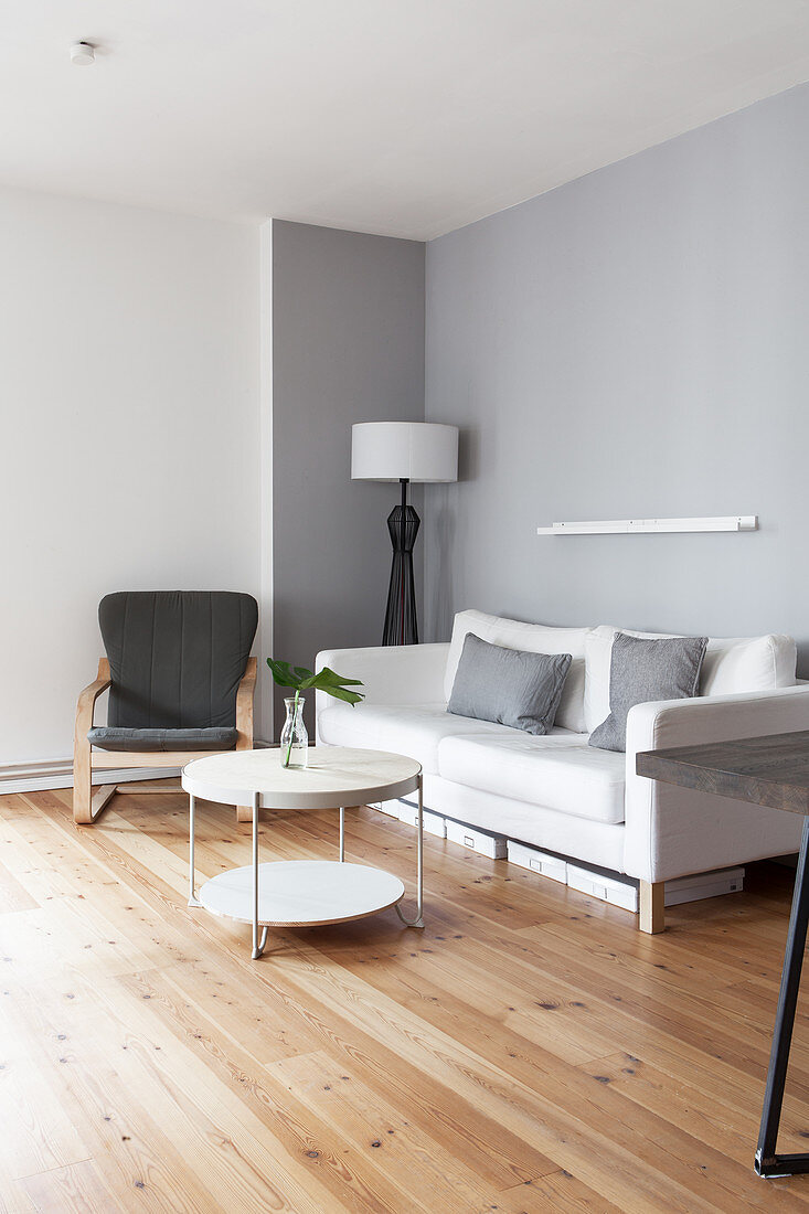 White sofa, armchair and round coffee table in grey-and-white living room