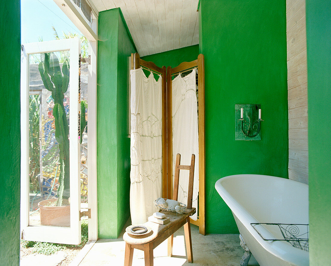 Free-standing bathtub and screen in bathroom with green walls and access to terrace