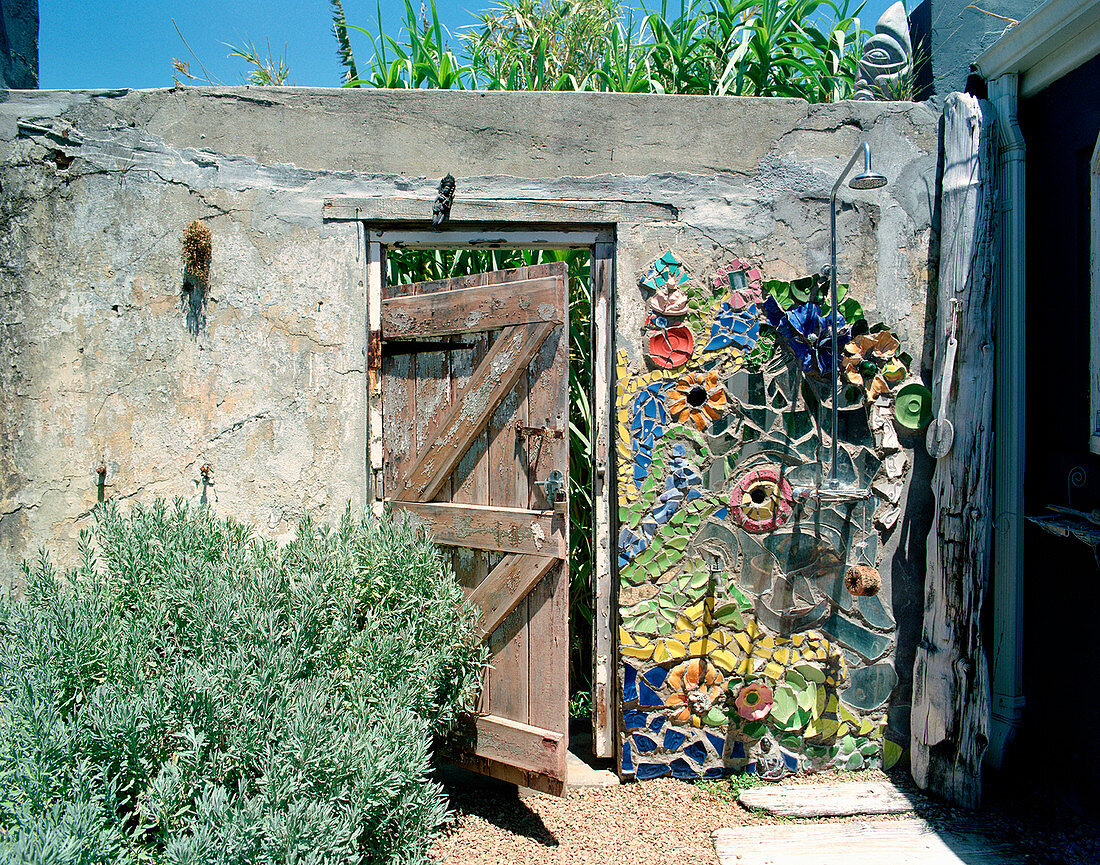 Artistically decorated stone wall with outdoor shower