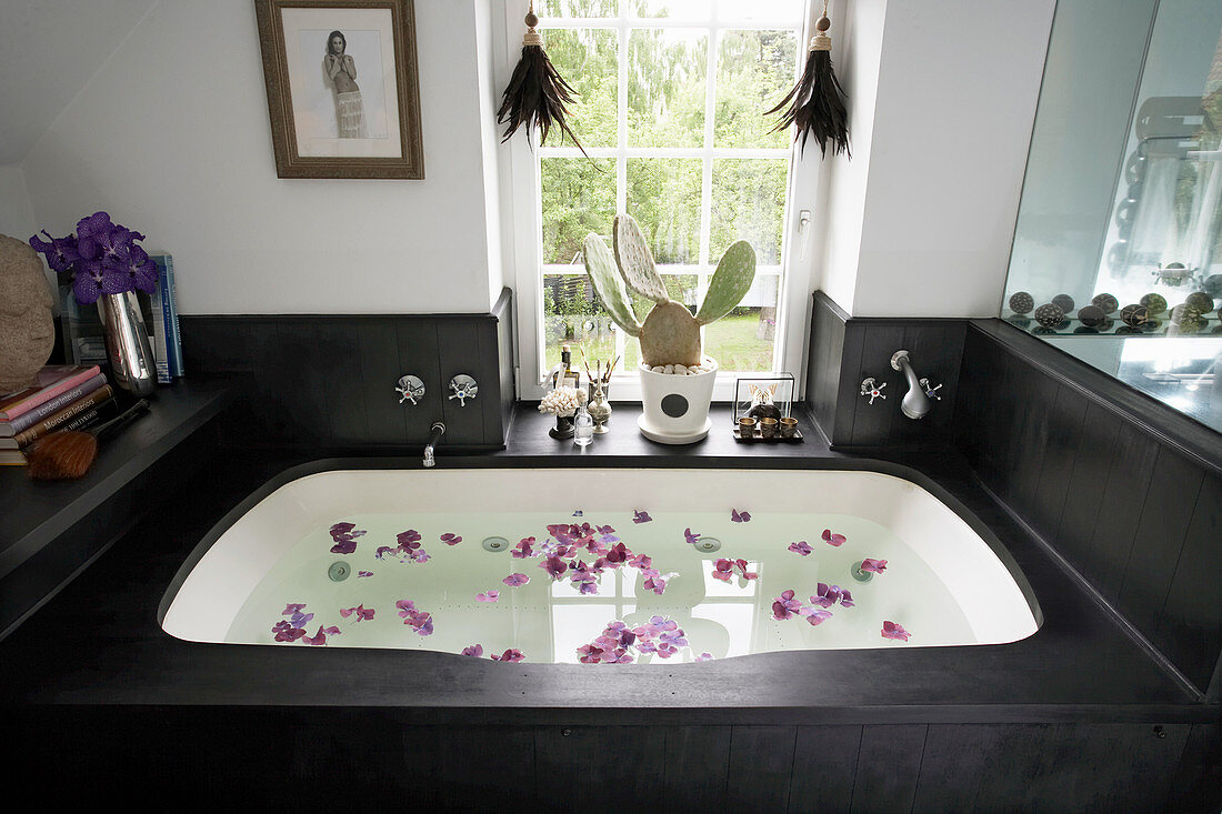 Rose petals floating in bathtub with black wooden surround