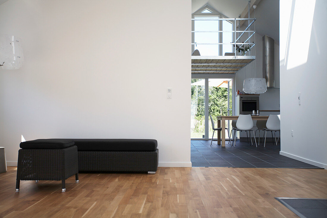 Black chaise and ottoman next to open doorway in loft apartment