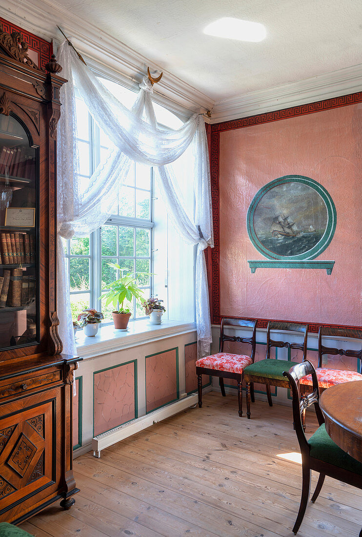 Chairs against a pink wall next to a window