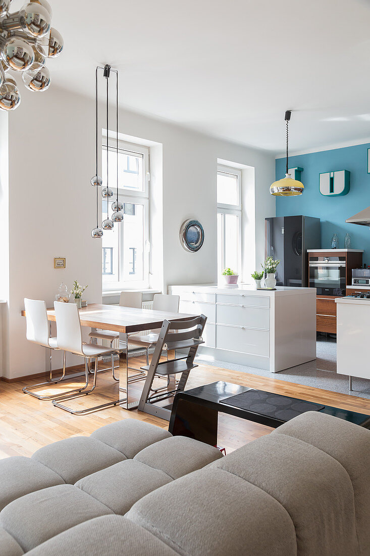 A kitchen with a light-blue wall, a dining area and a couch in an open-plan living room