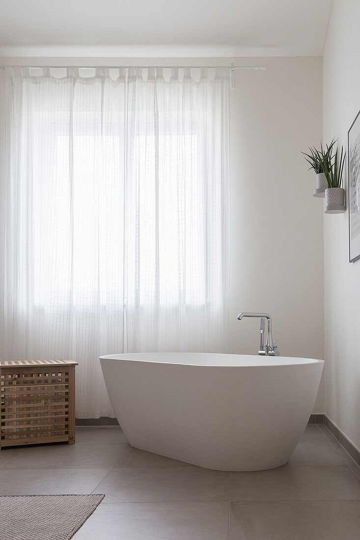A freestanding bathtub in front of a curtained window in a bathroom