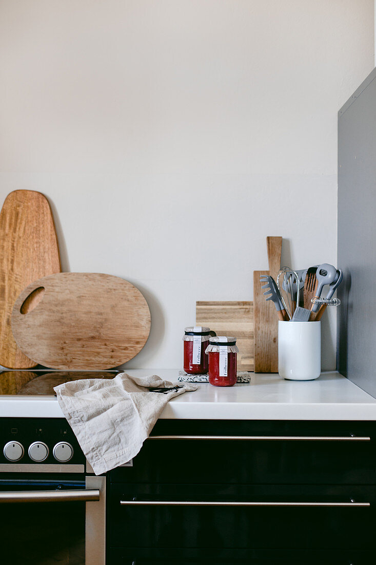Jam jars with DIY labels, kitchen tools and wooden boards on kitchen countertop