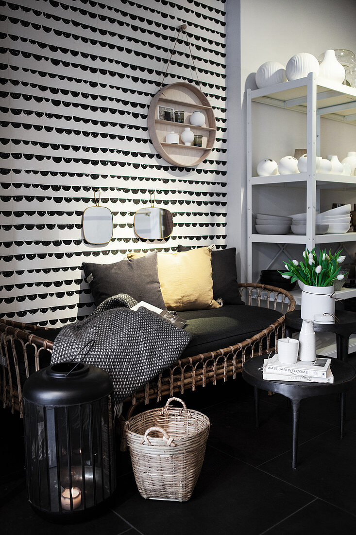 Rattan bench with cushions in front of wall hanging