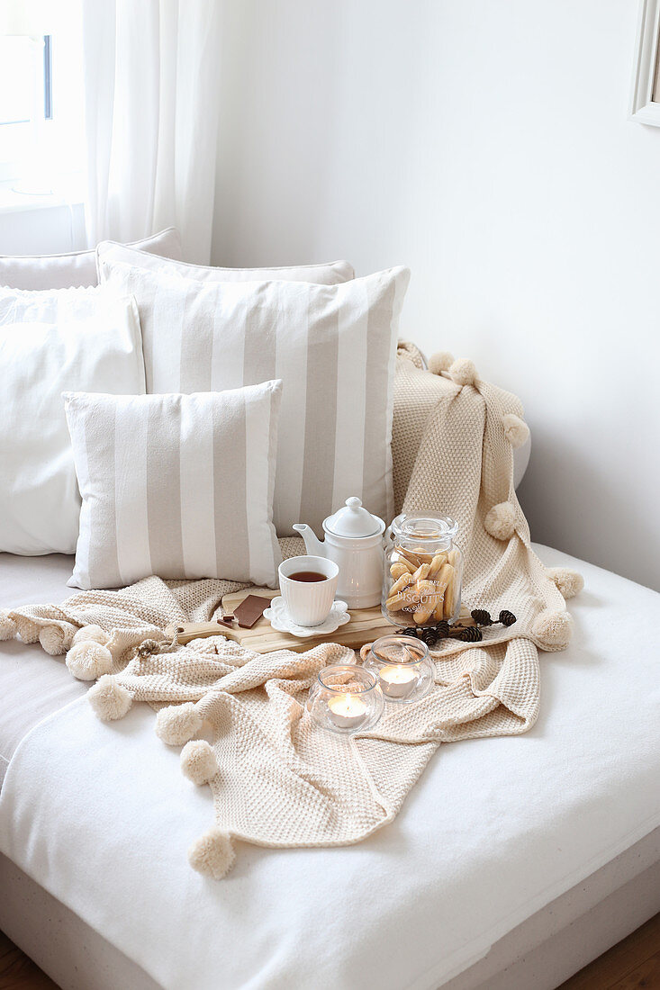 Wooden board with tea, cookies and chocolate on bed