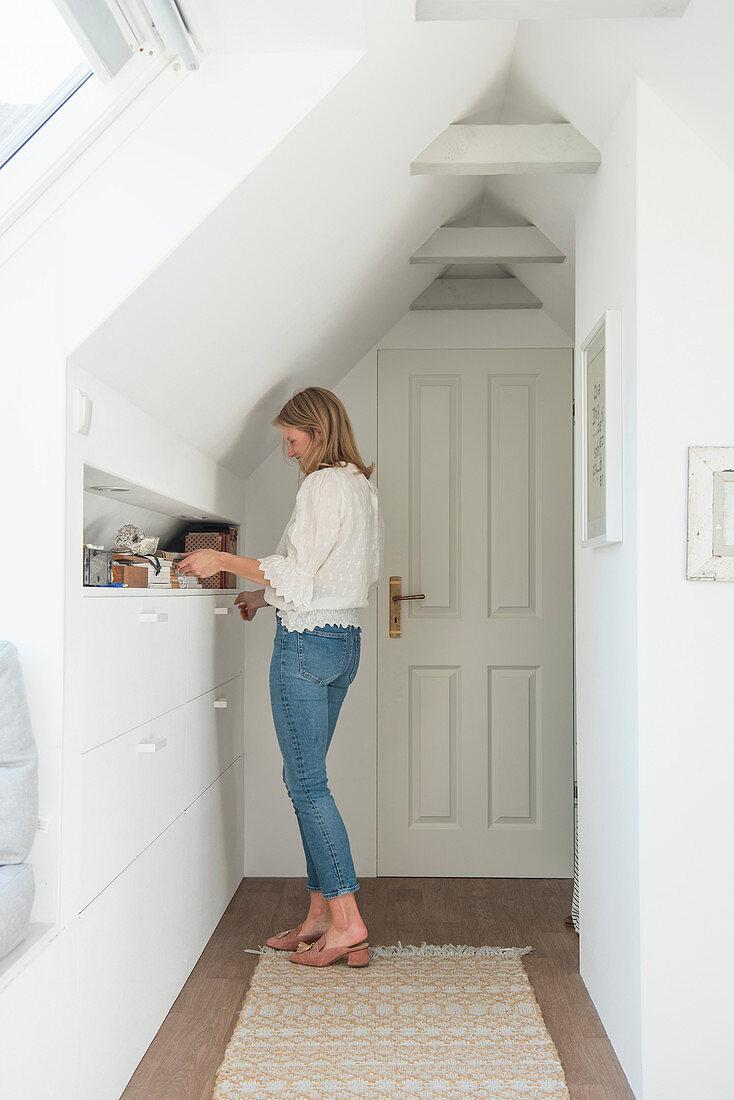 Blonde woman in front of shelf in niche in attic room