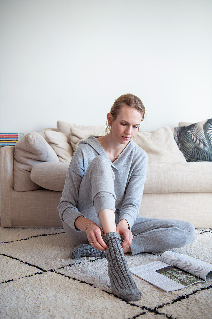 Blonde woman in casual wear reading magazine on the floor