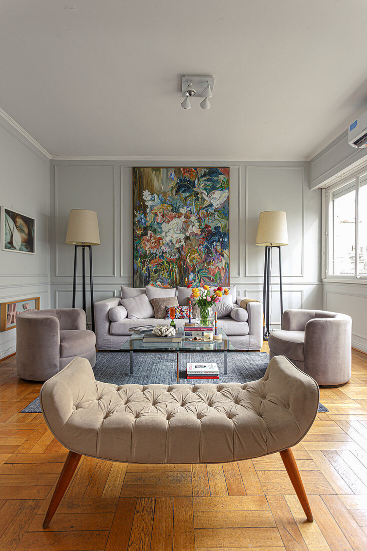 Pale upholstered furniture, standard lamps and paintings on coffered walls in living room