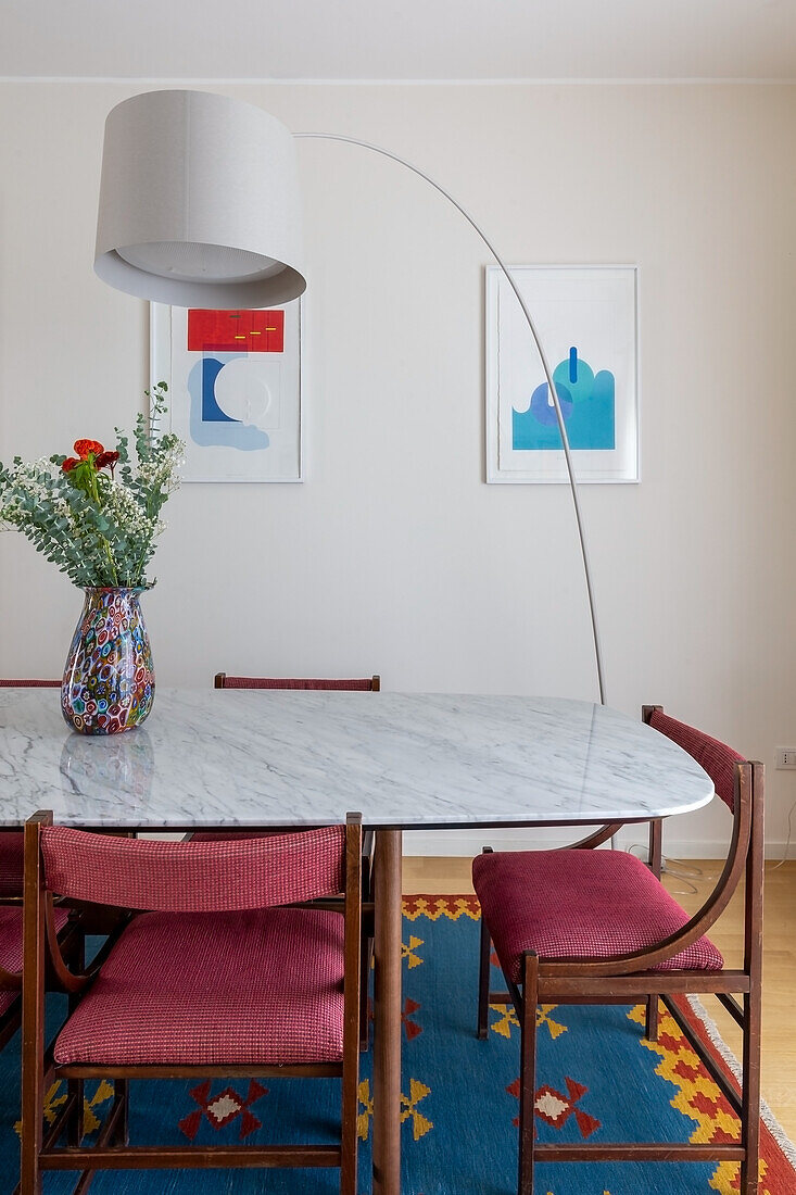 Arched lamp over dining table with marble top and upholstered chairs